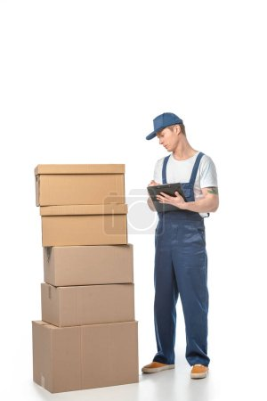 Photo for Partial view of handsome mover in uniform writing in clipboard near cardboard boxes isolated on white - Royalty Free Image