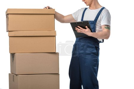 cropped view of mover in uniform holding clipboard near cardboard boxes isolated on white