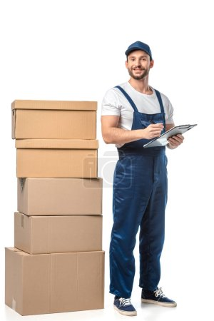Photo for Mover in uniform looking at camera while writing in clipboard near cardboard boxes isolated on white - Royalty Free Image