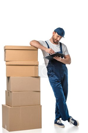 Photo for Mover in uniform writing in clipboard near cardboard boxes isolated on white - Royalty Free Image