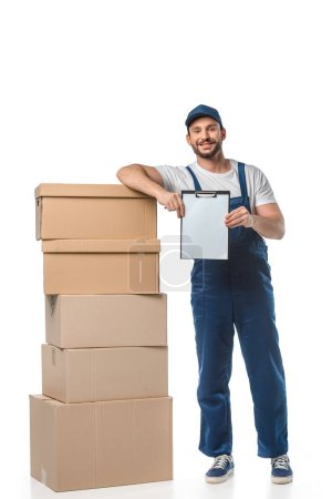 Photo for Handsome mover in uniform looking at camera while holding blank clipboard near cardboard boxes isolated on white - Royalty Free Image