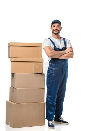 Photo for Handsome mover in uniform with cardboard boxes looking at camera and smiling isolated on white - Royalty Free Image