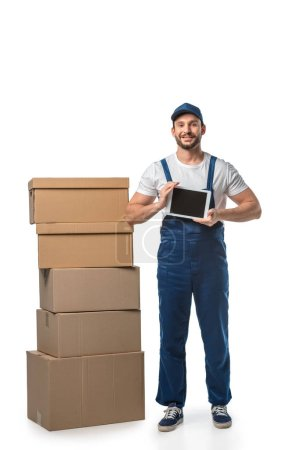 Photo for Mover with cardboard boxes looking at camera and presenting digital tablet with blank screen isolated on white - Royalty Free Image