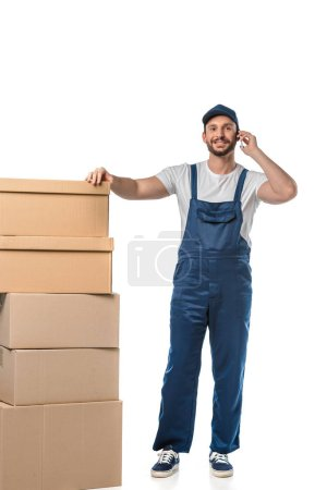 Photo for Handsome smiling mover with cardboard boxes talking on smartphone isolated on white - Royalty Free Image