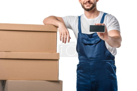 Photo for Partial view of smiling mover with cardboard boxes presenting smartphone with blank screen isolated on white - Royalty Free Image