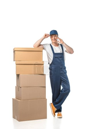 Photo for Handsome smiling mover in uniform with cardboard boxes talking on smartphone isolated on white - Royalty Free Image