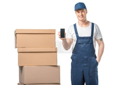 Photo for Smiling mover with cardboard boxes presenting smartphone with blank screen isolated on white - Royalty Free Image
