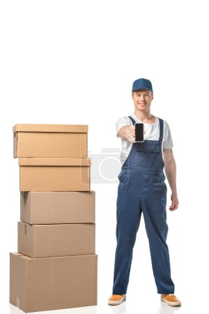 Photo for Smiling mover with cardboard boxes showing smartphone with blank screen isolated on white - Royalty Free Image