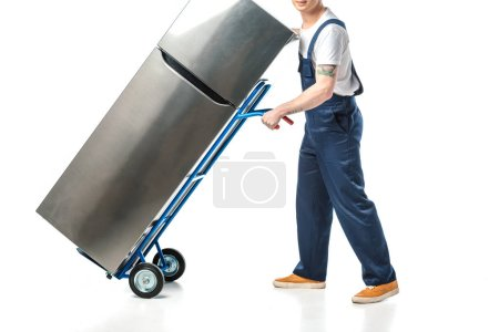 Photo for Cropped view of mover in uniform transporting refrigerator on hand truck isolated on white - Royalty Free Image