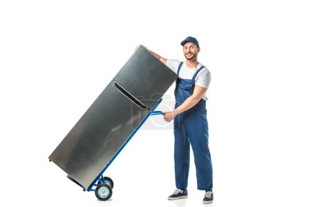 Photo for Handsome mover in uniform looking at camera and transporting refrigerator on hand truck isolated on white - Royalty Free Image