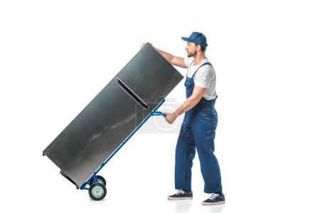 Photo pour Beau déménageur en uniforme transportant réfrigérateur sur camion à main isolé sur blanc - image libre de droit