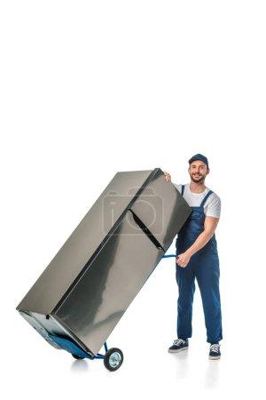 Photo pour Déménageur beau en unifrom regardant l'appareil-photo et transportant le réfrigérateur sur le camion de main isolé sur le blanc avec l'espace de copie - image libre de droit