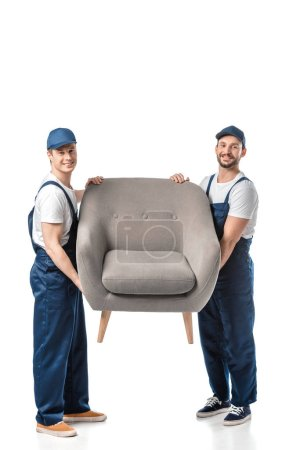 Photo for Two smiling movers looking at camera and transporting grey armchair isolated on white - Royalty Free Image