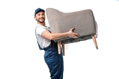 Photo pour Beau déménageur en uniforme regardant la caméra tout en transportant fauteuil gris isolé sur fond blanc - image libre de droit