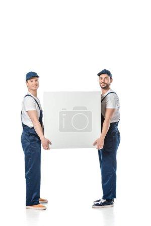 deux déménageurs souriants regardant la caméra tout en tenant boîte vide isolé sur blanc