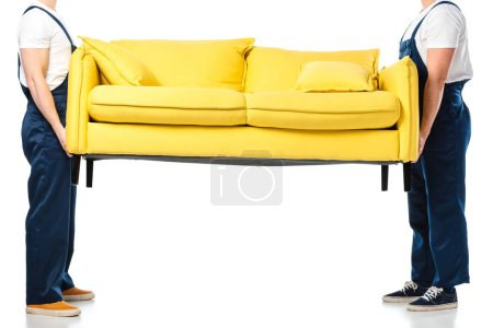 Photo for Cropped view of two movers transporting yellow sofa on white - Royalty Free Image