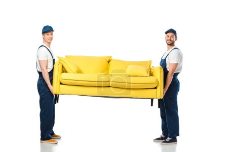 Photo for Two smiling movers transporting yellow sofa and looking at camera on white - Royalty Free Image