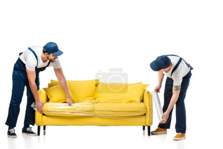 Foto de Dos movilizando un sofá amarillo con rollo de película elástica en blanco - Imagen libre de derechos