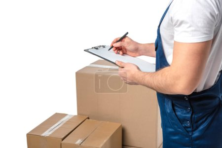 Photo for Partial view of mover in uniform writing in clipboard near cardboard boxes isolated on white with copy space - Royalty Free Image