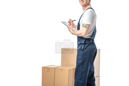 Photo for Cropped view of mover in uniform writing in clipboard near cardboard boxes isolated on white with copy space - Royalty Free Image