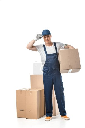 Photo for Handsome mover in uniform adjusting hat and looking at camera while carrying cardboard box isolated on white - Royalty Free Image
