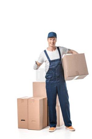 Foto de Guapo mover en la caja de cartón de transporte uniforme y mostrando el pulgar arriba signo aislado en blanco - Imagen libre de derechos