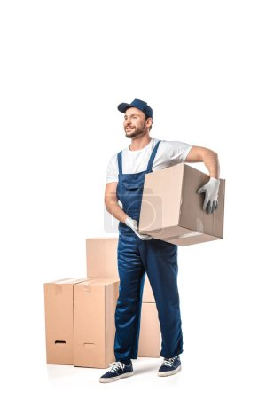 Photo for Handsome mover in uniform carrying cardboard box isolated on white - Royalty Free Image