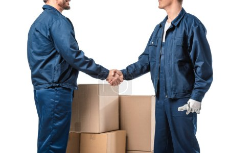 Photo for Cropped view of two movers in uniform shaking hands near cardboard boxes isolated on white - Royalty Free Image