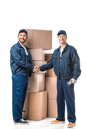 Photo for Two smiling movers in uniform looking at camera and shaking hands near cardboard boxes on white - Royalty Free Image