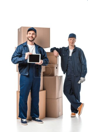 Photo for Two movers with cardboard boxes looking at camera and presenting digital tablet with blank screen on white - Royalty Free Image