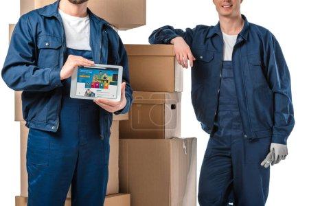 Photo pour Vue recadrée de deux déménageurs avec des boîtes en carton présentant la tablette numérique avec l'application d'Amazone sur l'écran isolé sur le blanc - image libre de droit