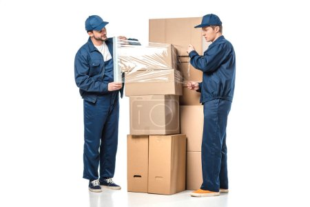 Photo for Two movers wrapping cardboard boxes with roll of stretch film on white - Royalty Free Image