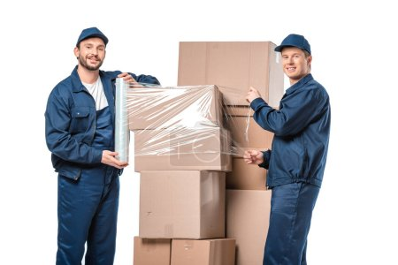 Photo for Two movers looking at camera and wrapping cardboard boxes with roll of stretch film isolated on white - Royalty Free Image