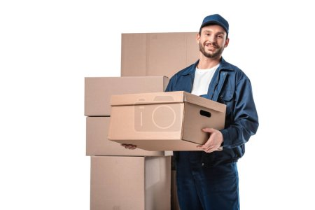 Photo for Smiling handsome mover in uniform carrying cardboard box and looking at camera isolated on white with copy space - Royalty Free Image