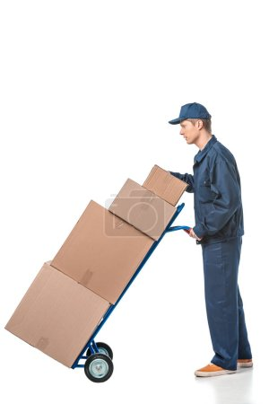 mover in uniform transporting cardboard boxes on hand truck isolated on white with copy space