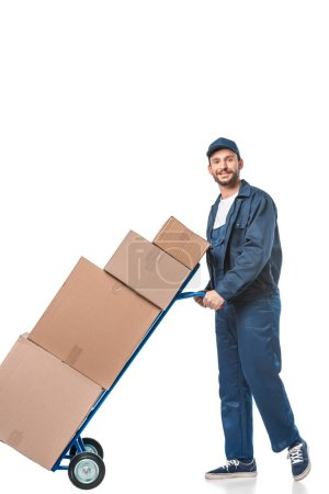 Photo for Smiling handsome mover in uniform transporting cardboard boxes on hand truck isolated on white - Royalty Free Image