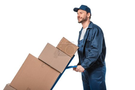 handsome mover in uniform transporting cardboard boxes on hand truck isolated on white with copy space