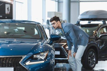 Stilvoller Mann mit Brille blickt auf Auto, während er im Autohaus steht