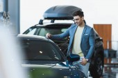 selective focus of happy customer in glasses standing near automobile in car showroom