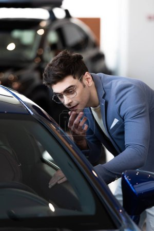 Photo for Pensive customer in glasses looking at automobile while standing in car showroom - Royalty Free Image