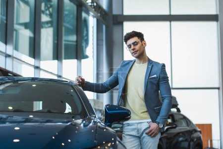 Photo for Pensive man in glasses standing with hand in pocket near automobile in car showroom - Royalty Free Image