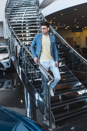 Photo for Stylish man in glasses walking down stairs in car showroom - Royalty Free Image