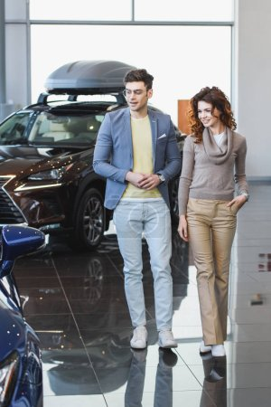 Photo for Stylish man in glasses walking in car showroom near curly attractive woman with hand in pocket - Royalty Free Image
