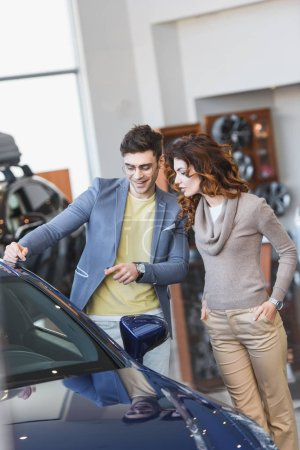 Photo for Happy stylish man in glasses pointing with finger at automobile near attractive woman with hands in pockets - Royalty Free Image