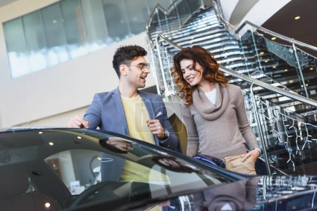 Photo for Stylish man in glasses pointing with finger at car near curly attractive woman standing with hand in pocket - Royalty Free Image