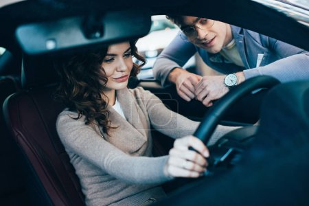 Photo for Selective focus of beautiful curly woman sitting in car and holding steering wheel near cheerful man in glasses - Royalty Free Image
