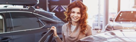 Photo for Panoramic shot of happy curly woman smiling while standing near vehicle in car showroom - Royalty Free Image