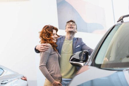 Photo for Selective focus of happy man hugging curly woman in car showroom - Royalty Free Image