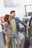 happy man hugging curly attractive woman standing with hand in pocket in car showroom