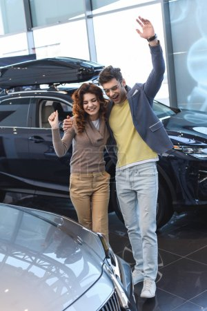 happy man hugging curly attractive woman while celebrating triumph in car showroom